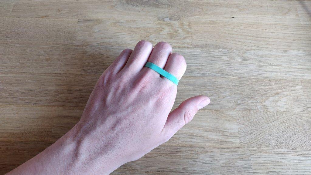 Ein Gummiband wird um dein Zeige- und Mittelfinger gelegt.