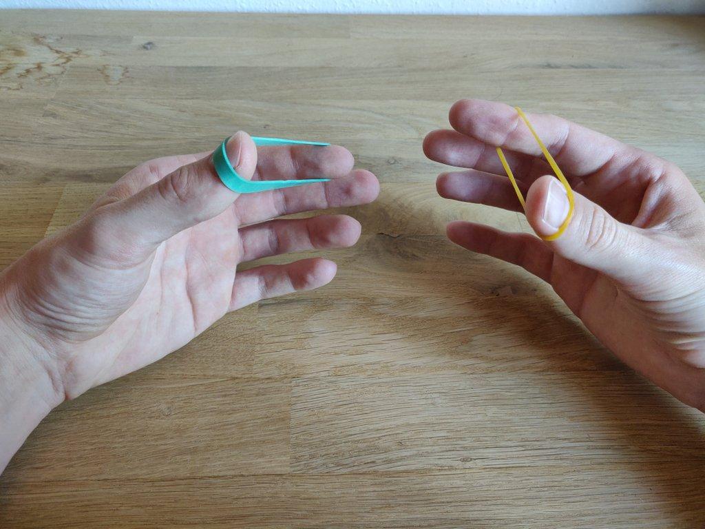 Die Gummis spannst du wie gezeigt zwischen Daumen und Zeigefinger.