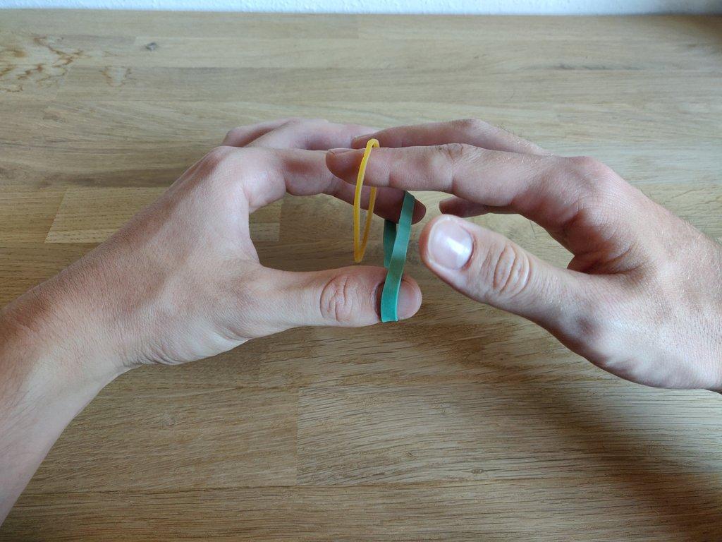Halte das rechte Gummiband wie gezeigt und verkette sie miteinander.