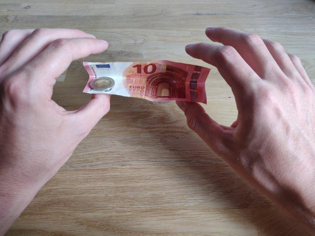Halte den Geldschein wie gezeigt mit deinen beiden Daumen.