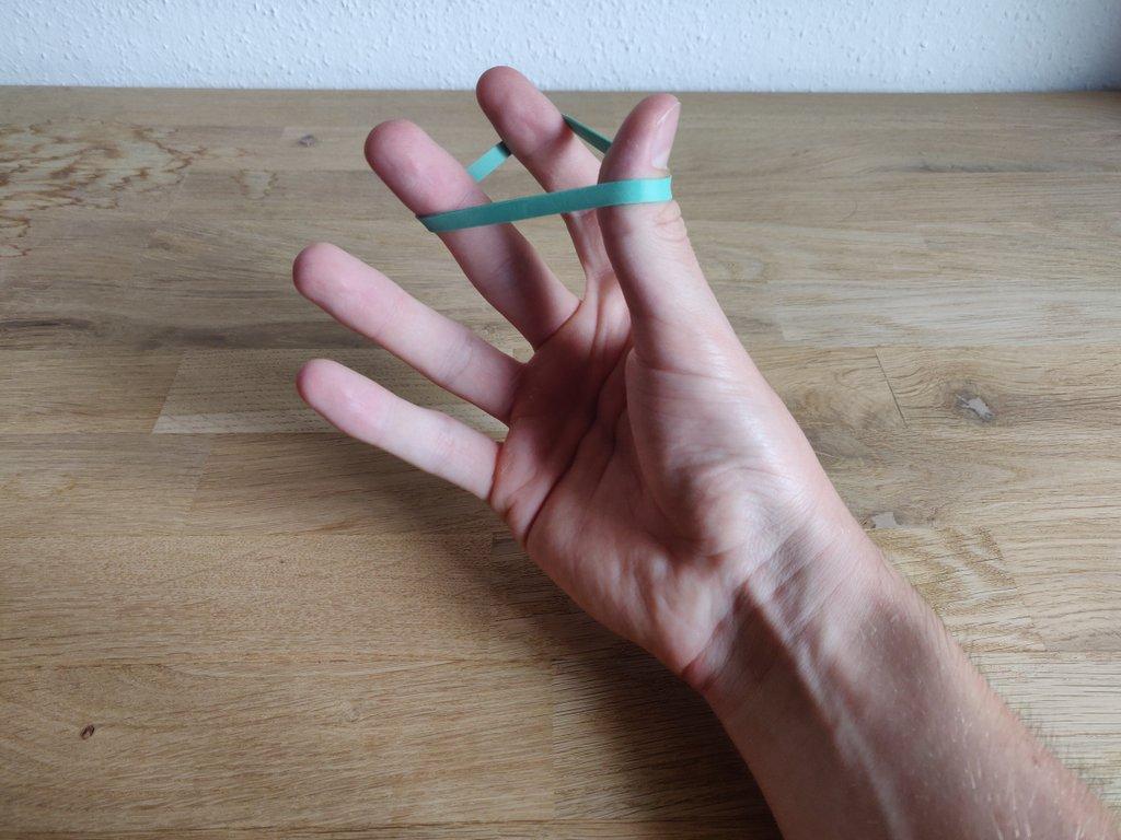 Lege das Gummi wie gezeigt um deine Finger.