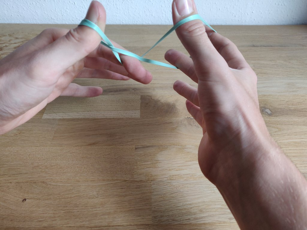 Drehe den linken Zeigefinger unter dem Gummi hindurch.