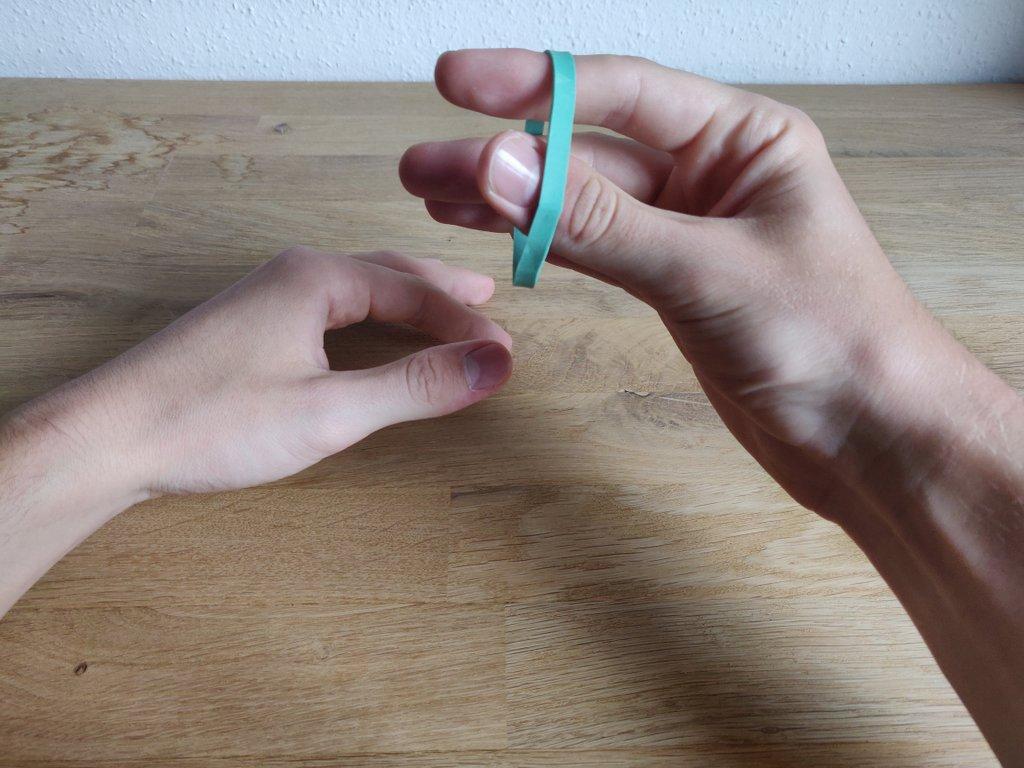 Auf sein Kommando durchdringt das Gummi seinen Finger.
