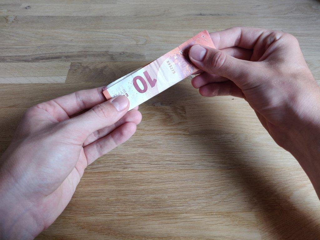 Wenn der Schein leicht schräg ist, rutscht die Münze von alleine in deine Hand.