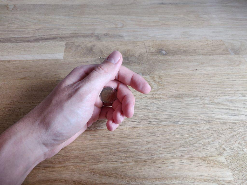 Die Münze befindet sich palmiert in der linken Hand.