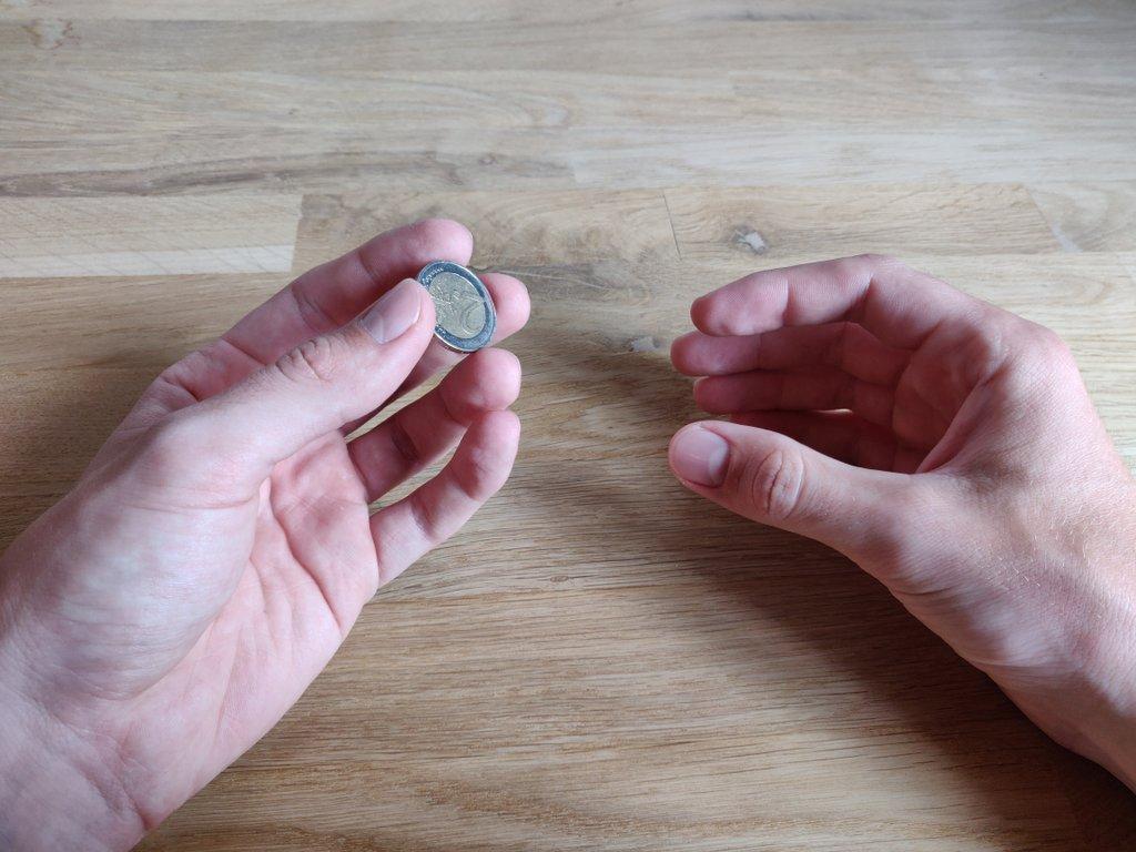 Die Münze befindet sich in deiner linken Hand zwischen Daumen, Mittel- und Zeigefinger.