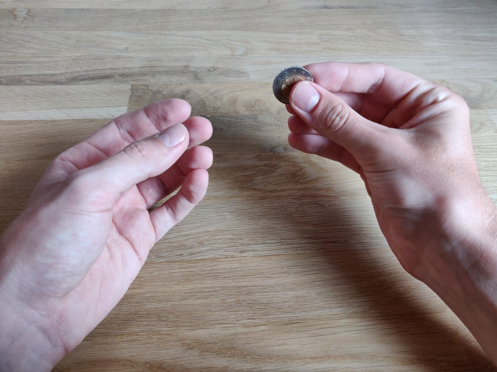 Die Münze befindet sich in der rechten Hand.