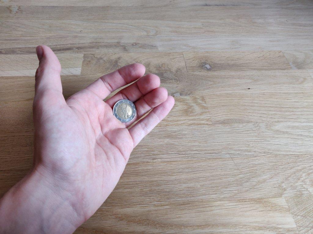 Winkle deine Finger wie gezeigt an,die Münze klemmt so zwischen Handballen und Fingern.
