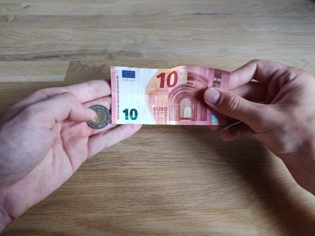 Lege den Geldschein auf die Finger der linken Hand.