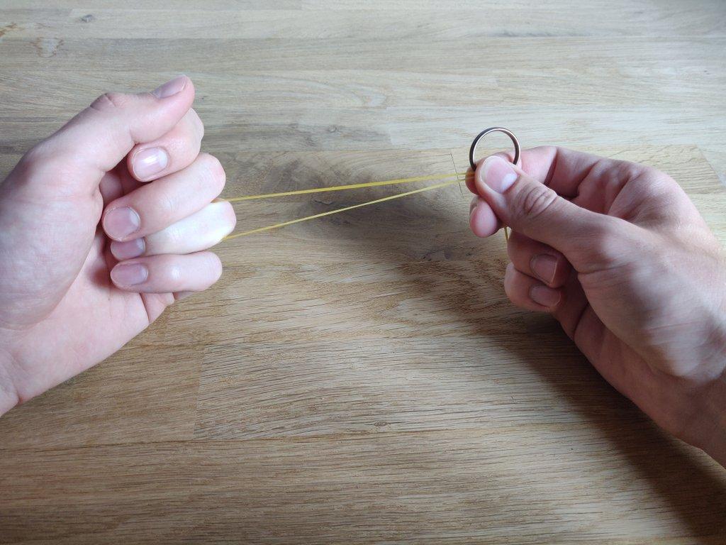 Greife mit dem Daumen und Zeigefinger der rechten Hand nach dem Ring und halte ihn fest.