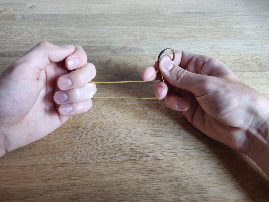 Den rechten Zeigefinger legst du von oben auf das Gummi.