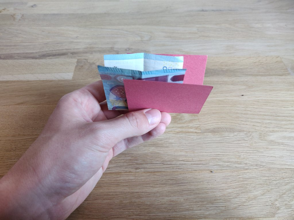 Ein Geldschein und ein Papier werden gefaltet und ineinander gelegt.