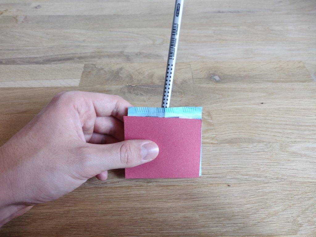 Stecke von oben den Stift durch den Schnitt des Geldscheins.