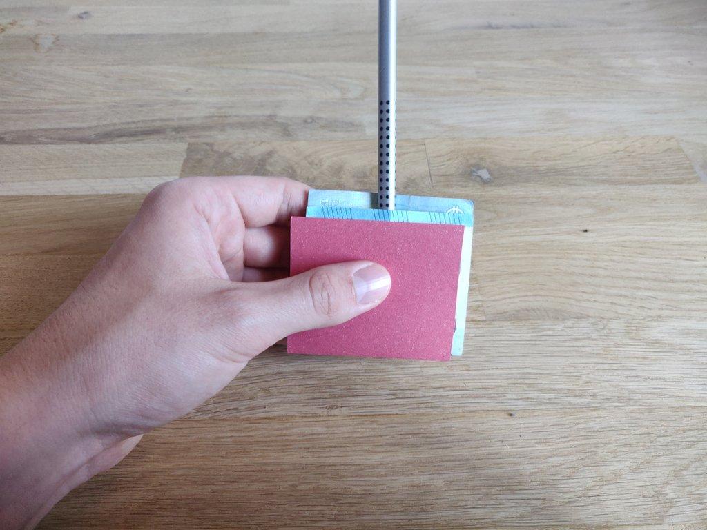 Ein Stift wird mittig auf den Geldschein gelegt...