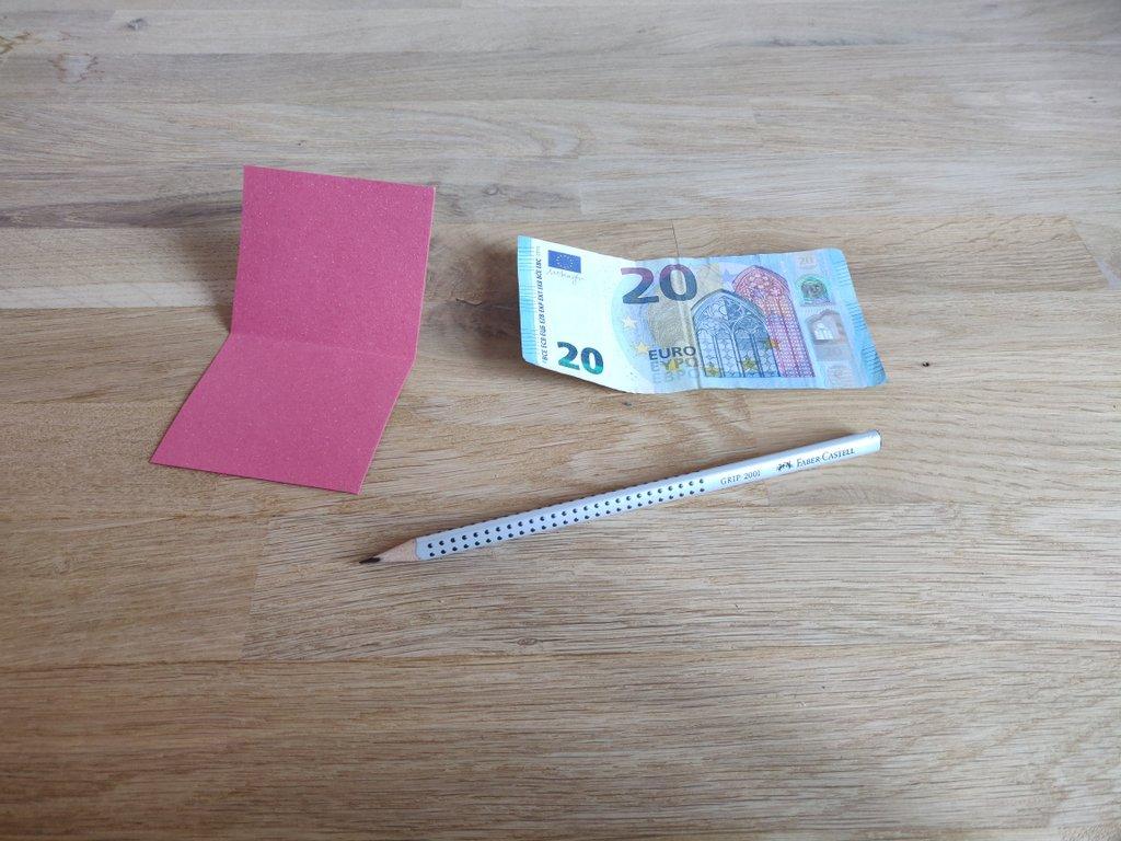 Du brauchst einen Stift, eine Schere und einen Geldschein.