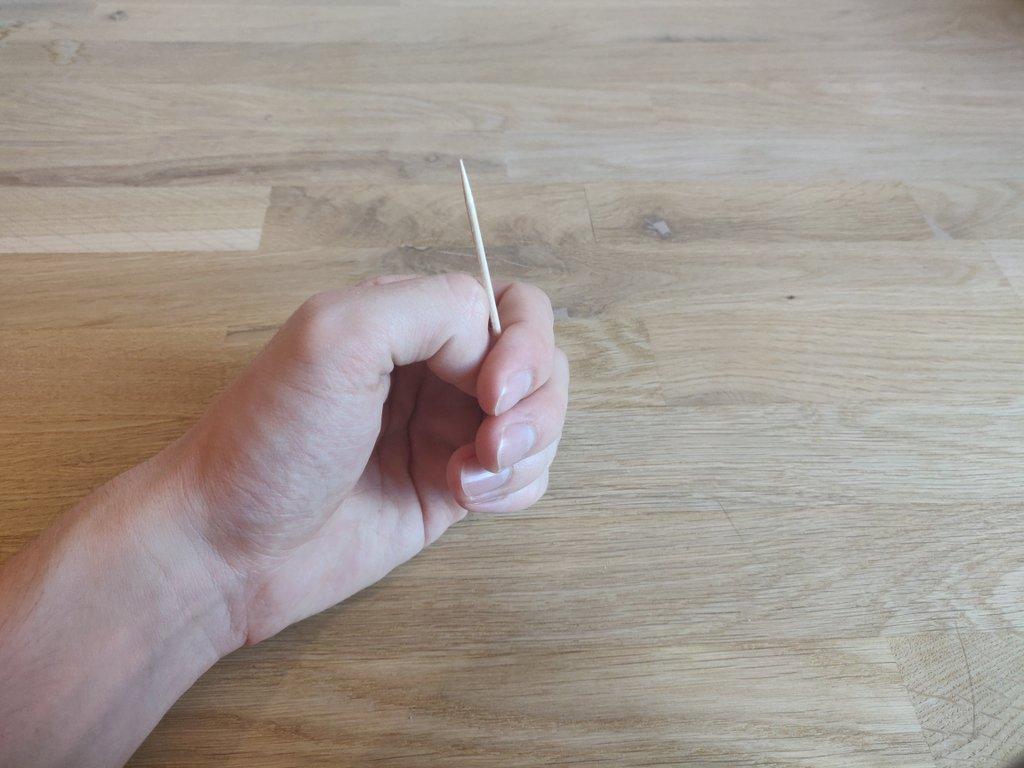 Verstecke das Klebeband mit deinem Mittel- und Zeigefinger.