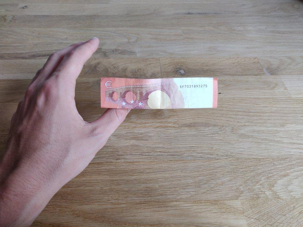 Der Geldschein schwebt auf dem Daumen...